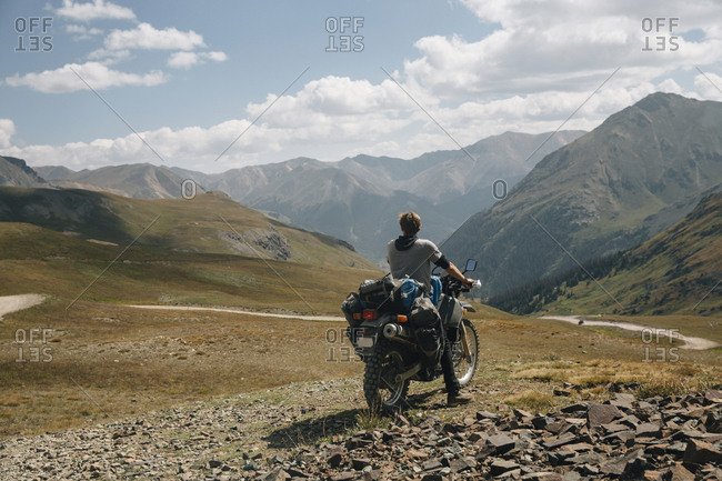 Rear view of biker riding motorbike on mountain against cloudy sky