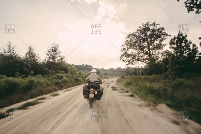 Rear view of biker wearing crash helmet while riding motorcycle on dirt road against sky