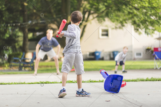 Rear view of boy playing baseball with father and brother at park