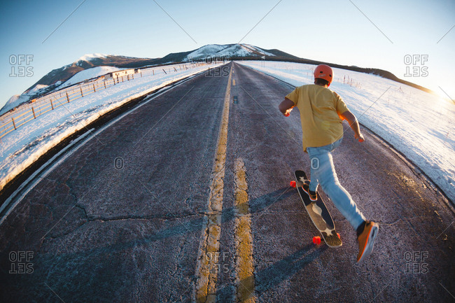 Rear view of man skateboarding on road amidst snow covered field against clear sky