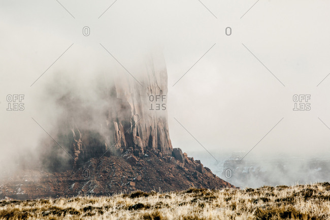 Rock formation at Monument Valley during foggy weather