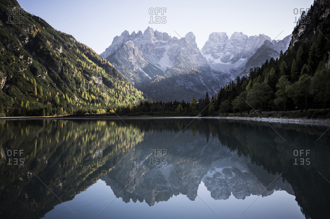 Scenic view of calm lake amidst mountains against sky