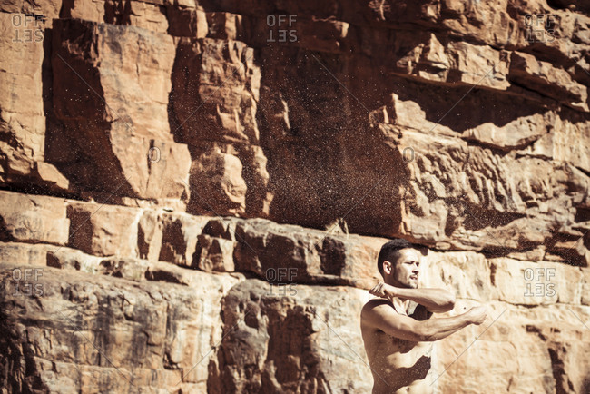 Shirtless Man dancing against rock formations during sunny day