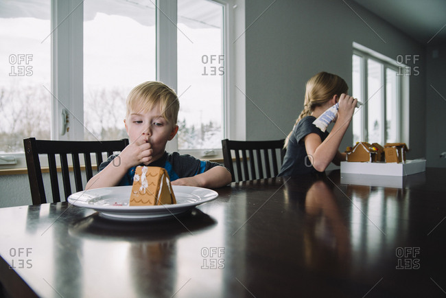 Siblings making gingerbread house while sitting at home during Christmas