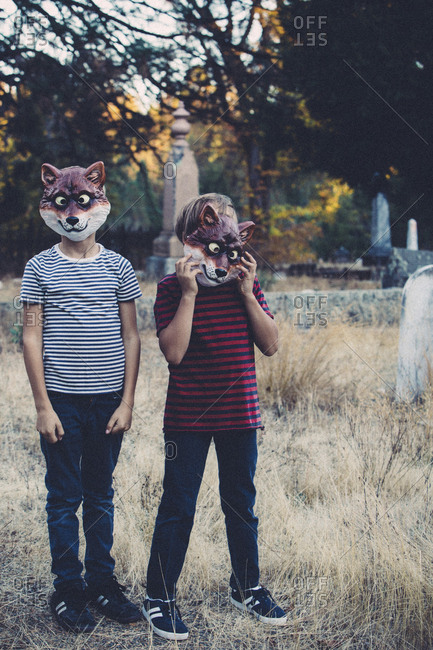 Siblings wearing animal masks while standing at cemetery