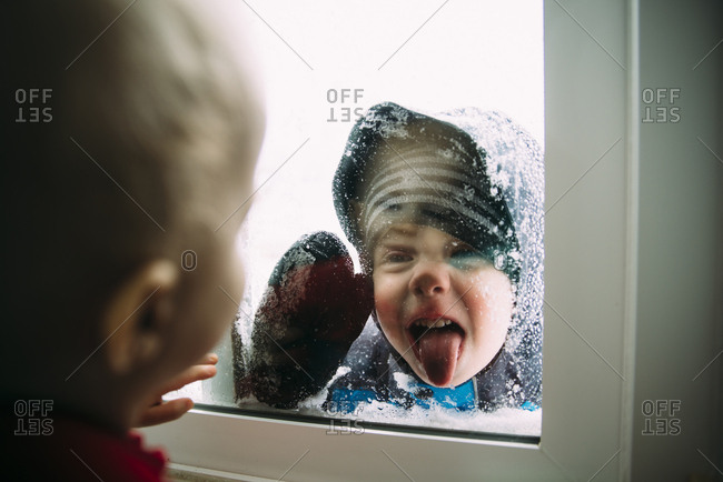 Side view of baby boy looking at brother sticking out tongue through window during winter