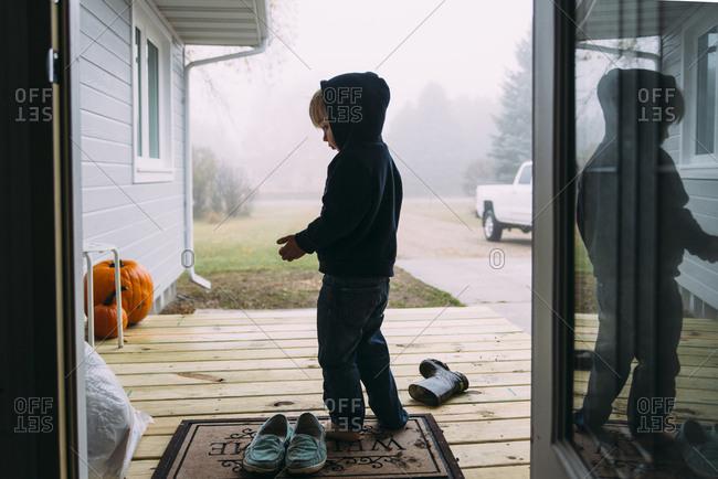 Side view of boy in hooded shirt seen through doorway