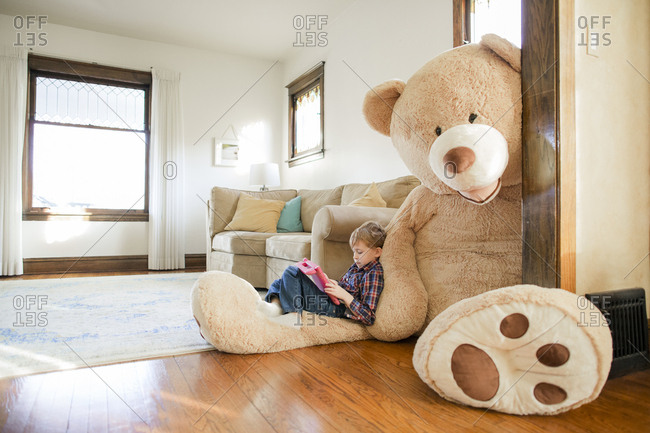 Side view of boy playing game while sitting on large teddy bear at home