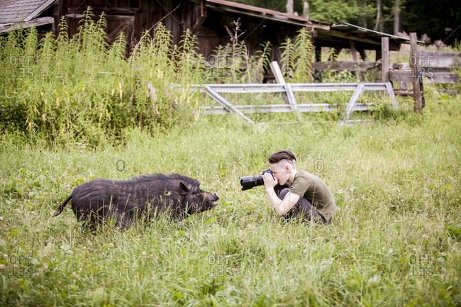 Side view of teenage boy photographing wild boar