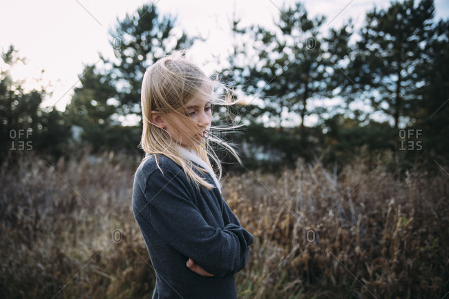 Side view of thoughtful girl with arms crossed standing on grassy field
