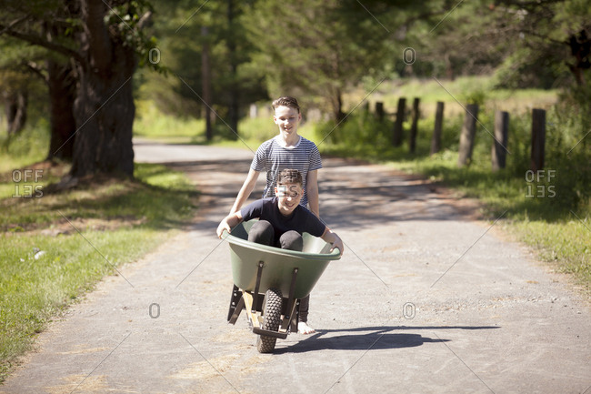 Teenage boy carrying brother in wheelbarrow on road