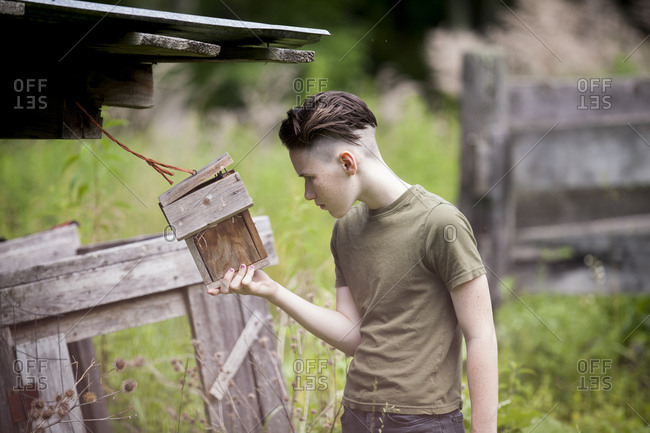 Teenage boy holding birdhouse while standing on field
