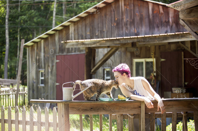 Woman kissing cat while standing by railing against wooden cabin
