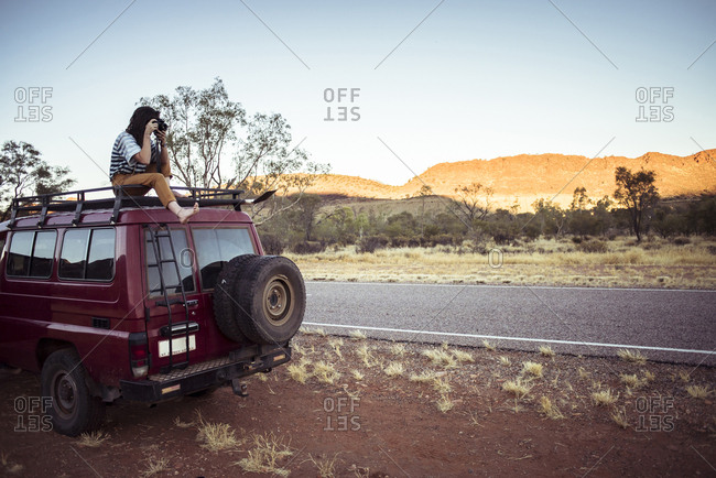 Woman photographing while sitting on car roof at desert