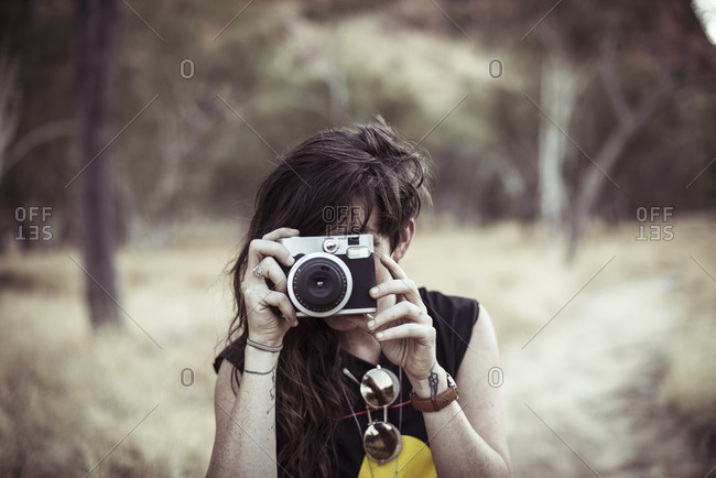 Woman photographing while standing at desert