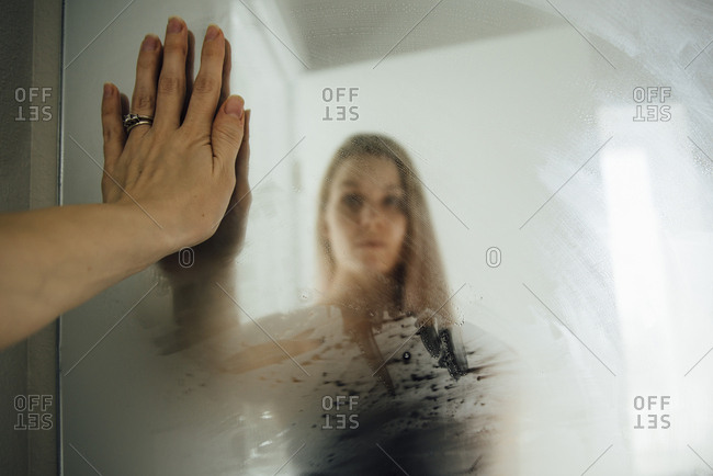 Woman reflecting on wet mirror at home
