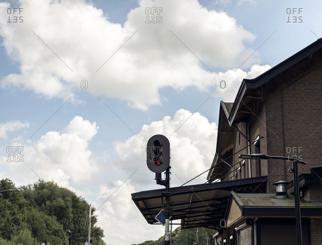 Red signal light at train station with blue cloudy sky