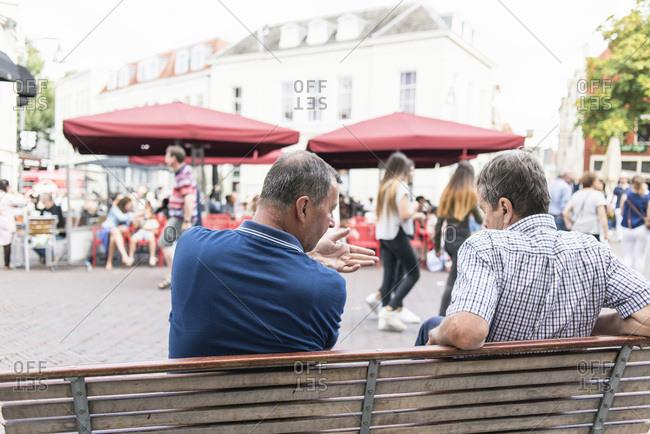 Deventer, Netherlands - September 4, 2017: Two men talking while sitting on bench