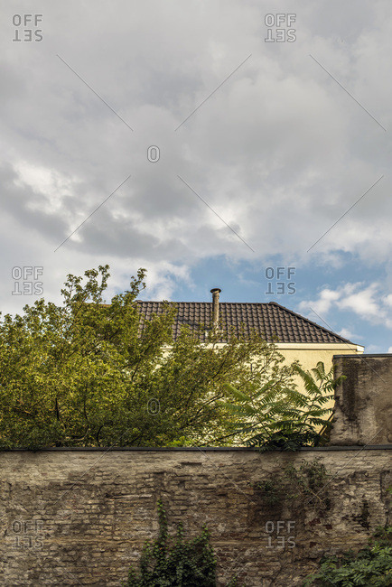 Old brick fence with trees and house under cloudy sky