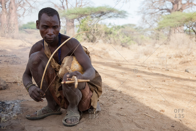 Tanzania, Africa - October 15, 2014: Hadzabe Tribe, adult local man playing a traditional instrument, Tanzania, Africa