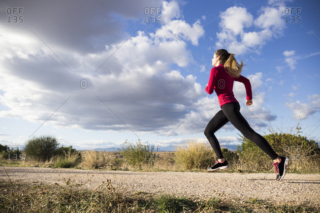 Side view of pretty woman jogging on road in countryside