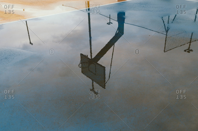 Basketball hoop reflected in puddle