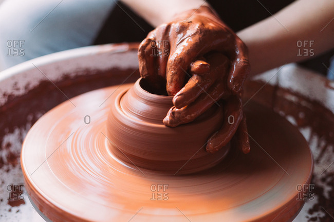 Hands shaping clay on wheel