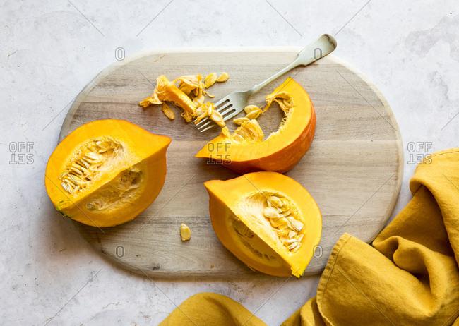 Raw kuri pumpkin sliced on a cutting board