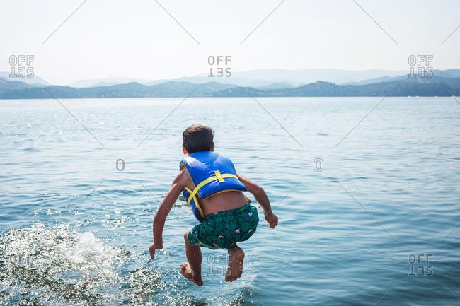 Boy wearing life vest jumping into lake