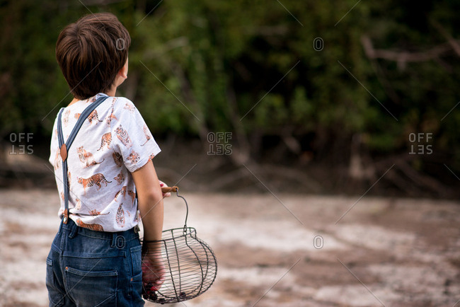 Rear view of boy holding a basket with fresh picked blackberry