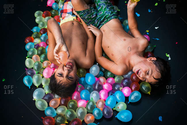 Two boys lying in a pile of water balloons on a trampoline