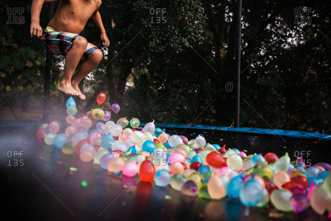 Child jumping on trampoline filled with water balloons