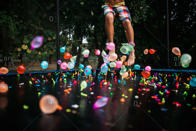 Boy jumping on trampoline with water balloons