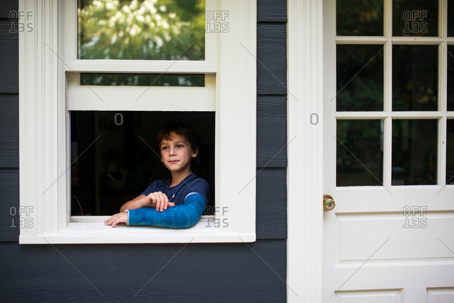 Little boy with blue arm cast looking out open window