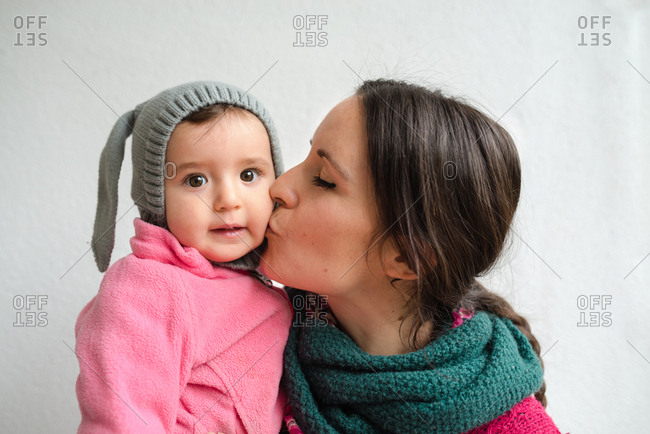 Mother kissing cute baby girl with rabbit hat
