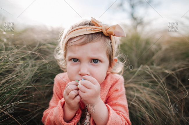 A little girl eating a candy necklace