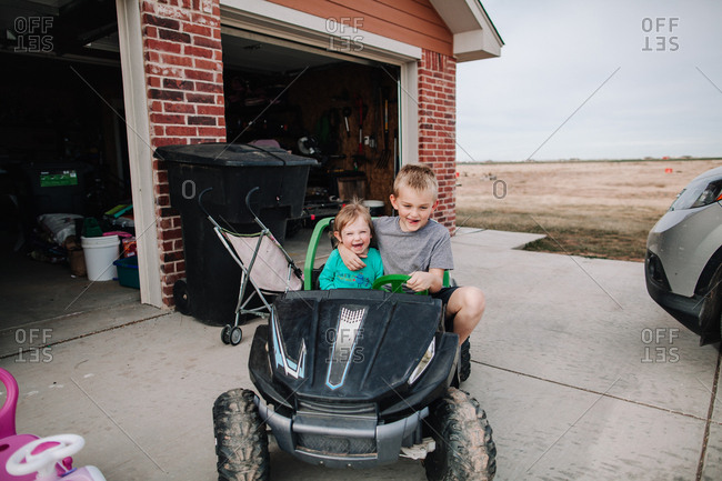 Boy and girl riding in a battery operated truck