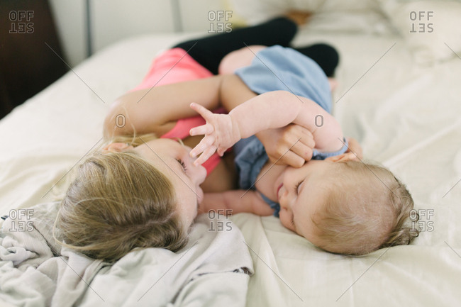 Girl lying on bed playing with baby sister