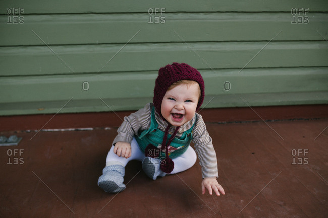 Laughing baby wearing a knit hat sitting on floor