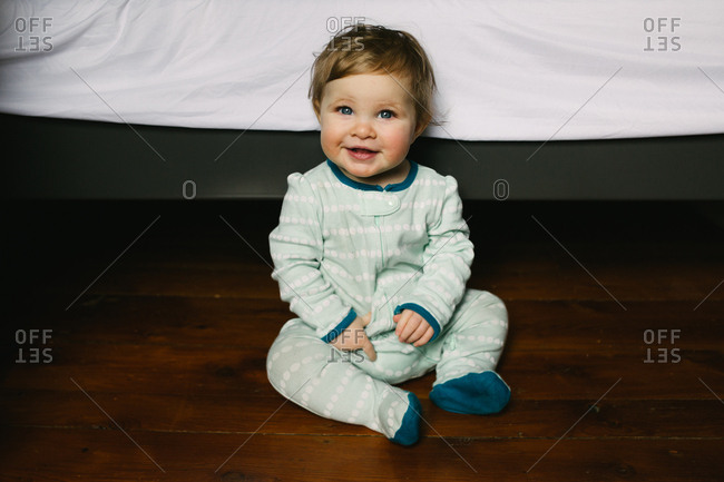 Smiling baby wearing pajamas sitting on floor