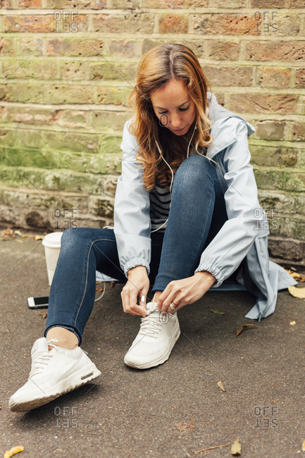 Blonde woman lacing her shoes and listening to music with her mobile phone and headphones in the street