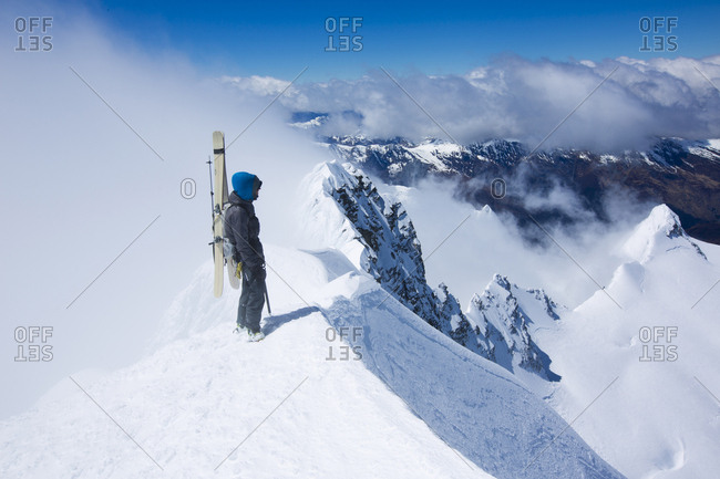 Beau Fredlund stands on a mountain top above the clouds as he prepares for his descent. South Island, New Zealand.