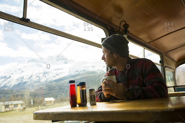 Brody Leven enjoys a hot cup of coffee on a train, while looking out the window and enjoying the snow capped mountain views. Patagonia, Chile.