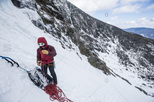 Front view of climber preparing ropes before climbing in Huntington Ravine, New Hampshire, USA
