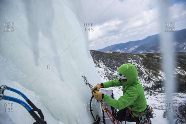 Climber checking ropes before ice climbing in Huntington Ravine, New Hampshire, USA