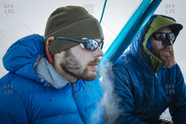 Two men sit in a tent in cold conditions on a glacier in Denali National Park and Preserve.