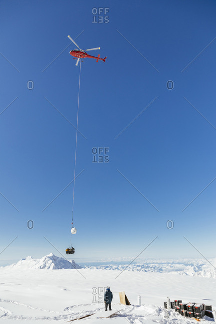 Helicopter delivering load to glacier camp, Denali National Park, Alaska, USA