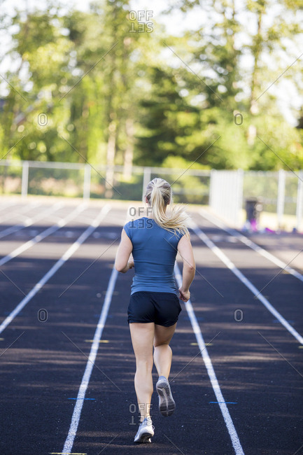 Rear view of female runner with ponytail working out on track, Eugene, Oregon, USA