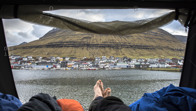View of Klaksvik town from tent and feet of relaxing tourist, Faroe Islands, Denmark