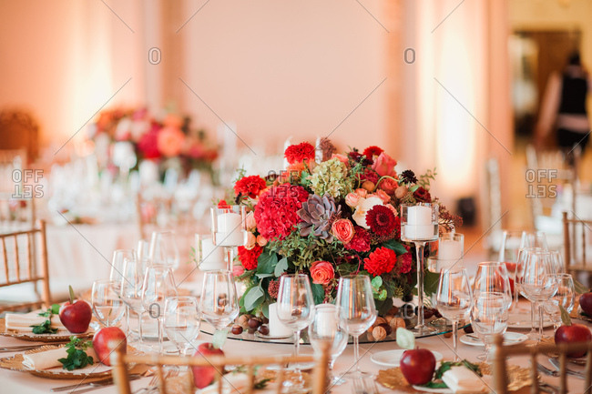 Floral centerpiece and place settings with apples served at wedding reception